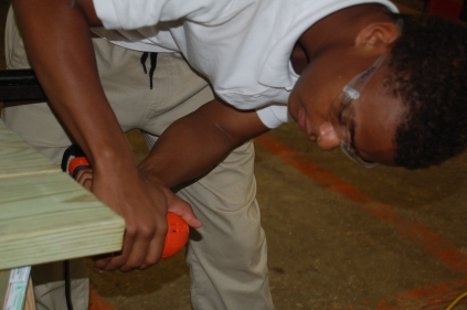 Jaylan Jones attaches the bolts to the picnic tables they are building.