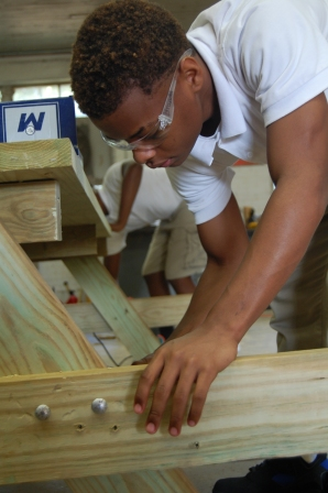 Jaylan Jones attaches the seat to one of the picnic tables being constructed.