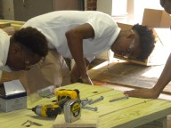 Lekeandre Smith and Emmantavious Ivory pre-drill the holes for the bolts going into the tables.
