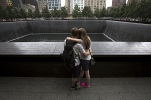 People embrace at the National September 11 Memorial and Museum in Lower Manhattan in New York, September 10, 2015. People from around the world visited the site on Thursday, the day before the 14th anniversary of the September 11 terrorist attacks. The 9/11 memorial and museum are located at the original site of the World Trade Center's North and South towers, which were destroyed in the attacks. REUTERS/Andrew Kelly TPX IMAGES OF THE DAY