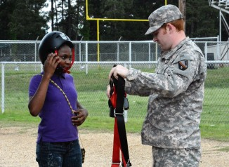 Army National Guard members assist students in harnessing themselves for the rock climbing wall.