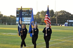 FFA members Daniela Miranda, Sandra Banuelos, and Carrie Driskill post the colors before the game for the national anthem.