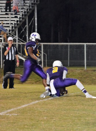 Kameria Alford kicks the ball as #2, Shaun Monroe sets up the field goal kick.