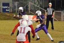 Jamarkell Ferrell blocks the defense as quarterback Shaun Monroe receives the snap.