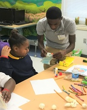 Chauncell Jenkins helps Tanyaha with the art project.
