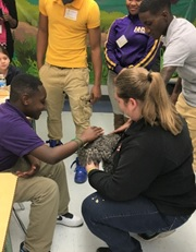 "Ms. Anderson holds ""Puffy"" while Chauncell Jenkins and Eddie pet him."